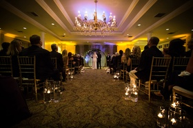 indoor wedding with warm lining, aisle lined by floating candles