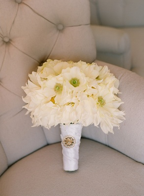 White flowers wrapped in ribbon with brooch