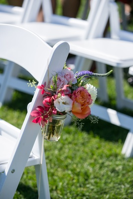 Pink and purple flowers in mason jar on white ceremony chair