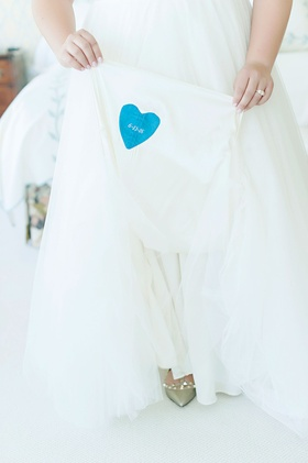 Bride holding up wedding dress something blue heart sewed into gown wedding date