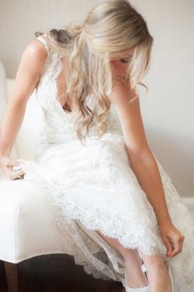 bride fastens shoes monique lhuillier wedding gown