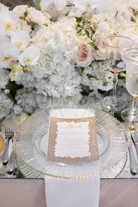 wedding reception personalized menu card calligraphy gold rimmed charger mirror table white flowers