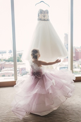 Flower girl in one shoulder dress with ombre purple skirt large bow ruffles looking at wedding dress