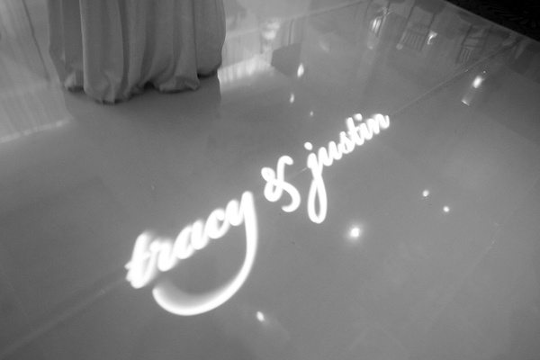 Black and white photo of couple's names projected onto dance floor