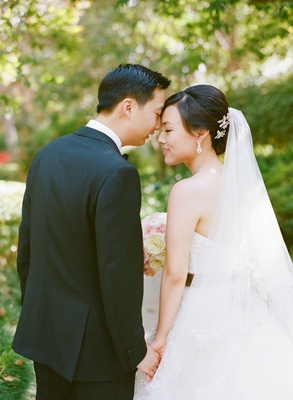 bride with updo and long veil holding hands with groom