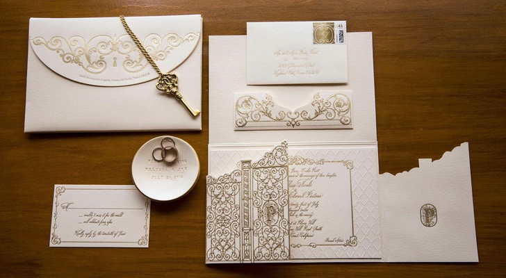 Antique gold key and monogrammed gate invite