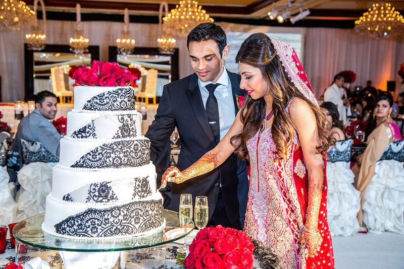 Indian bride and groom cut cake at reception