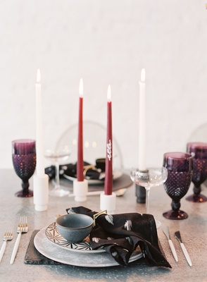 wedding reception metal table plate with black napkin white burgundy tall candles purple glassware