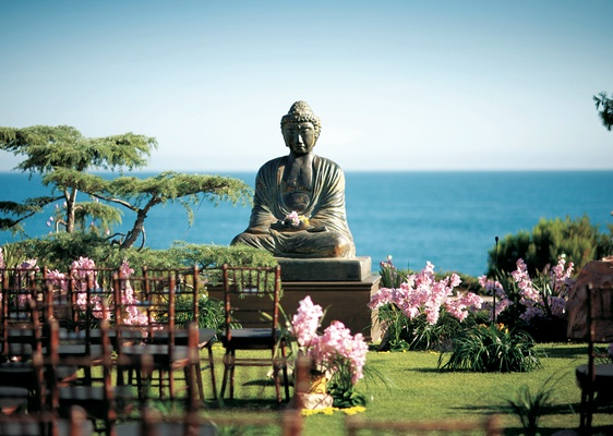 meditating buddha statue faces oceanfront ceremony