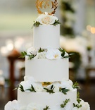 wedding cake round white tiers white orchid and rose flowers greenery gold laurel wreath cake topper