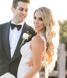 Groom smiles at bride long blonde hair with pearls draping along low back lace galia lahav open back