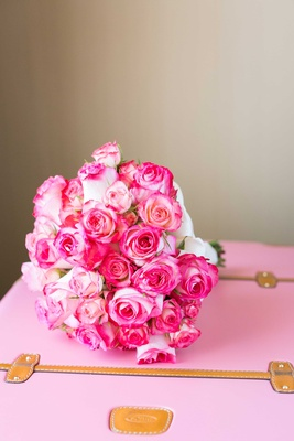 Hot pink and light pink rose bouquet Double Delight roses on baby pink camel leather suitcase