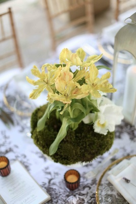 White vase with moss and yellow flowers at wedding