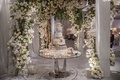 wedding cake on table multi layer feather silver white flowers greenery arch modern cake table