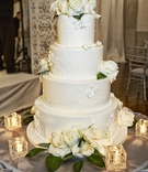Four layer cake with lace design and fresh flowers