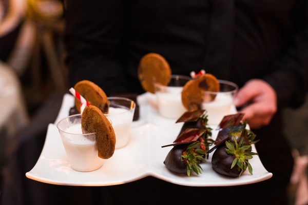 server carrying dessert tray with milk and cookies and chocolate-covered strawberries
