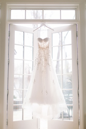 reem acra wedding dress strapless personalized hanger hanging in window french doors sunlight