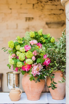 wedding reception in historic venue courtyard italy terracotta vase green flowers pink peony blooms