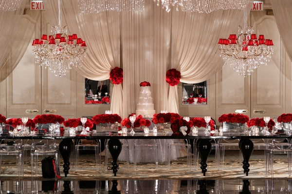 wedding reception white drapery chandelier red shade black modern table red roses low centerpieces