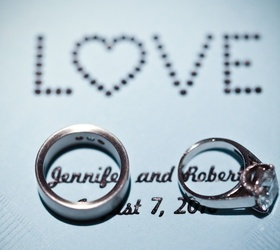 Bride engagement ring and men's band on LOVE napkin