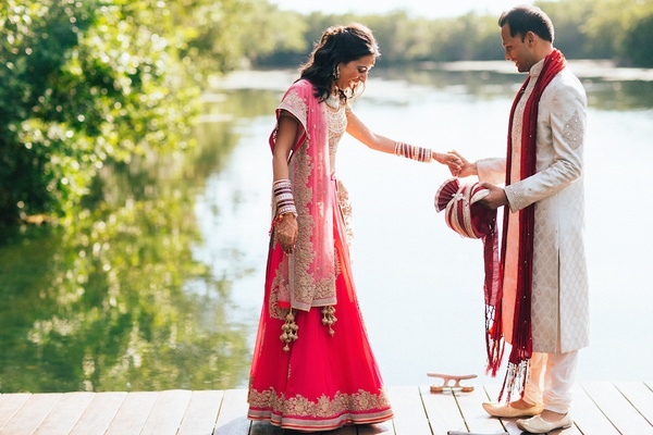 Indian bride in gold and magenta sari with groom in traditional white and red outfit