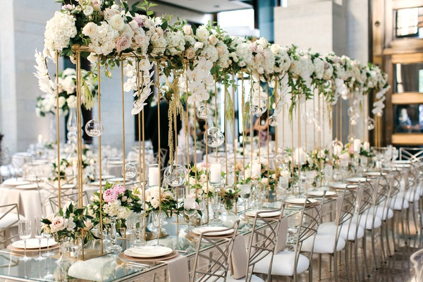 long glass tables with a floating garland runner on thin gold stands