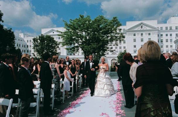 Father of the bride escorts bride down aisle