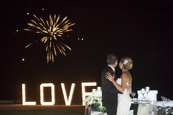 Bride and groom watching fireworks show over ocean at destination wedding in Mexico