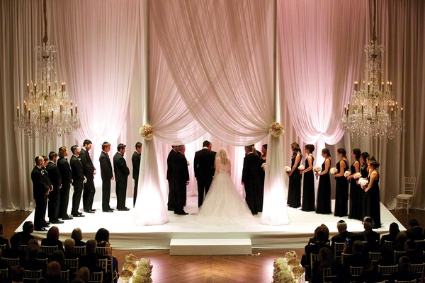 Bride in Vera Wang wedding dress under draped chuppah with bridesmaids groomsmen pink lighting