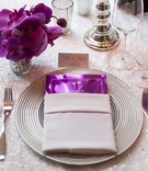 Metallic purple menu card in silver napkin on white sequin table