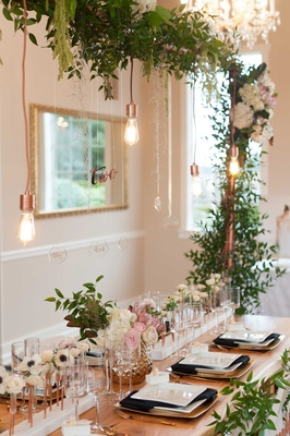 a unique modern and green tablescape head table with hanging lights arch copper color foliage