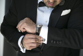 Groom in black tuxedo wears watch with black band, puts on circurlar cuff links
