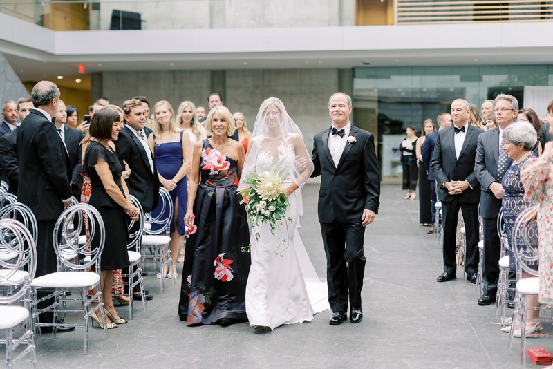 bride with veil over face walking down aisle with mother in flower print one shoulder gown father