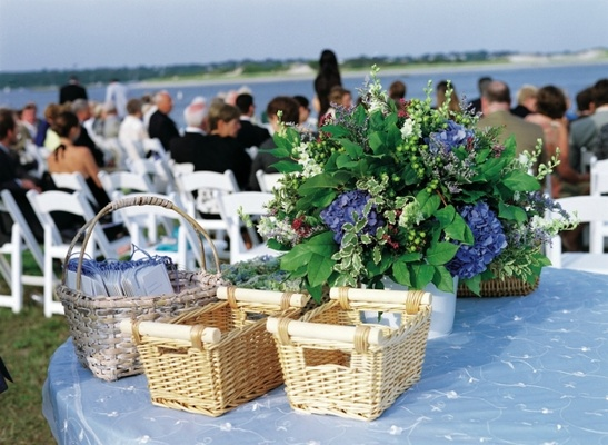 Blue linens on round table with wicker baskets at wedding