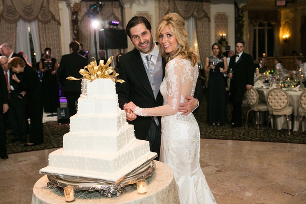 White wedding cake with square layers, piping looked like stacked Christmas presents, gold ribbon
