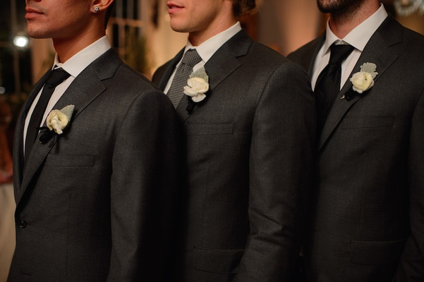 Three groomsmen in charcoal suits with mismatched ties