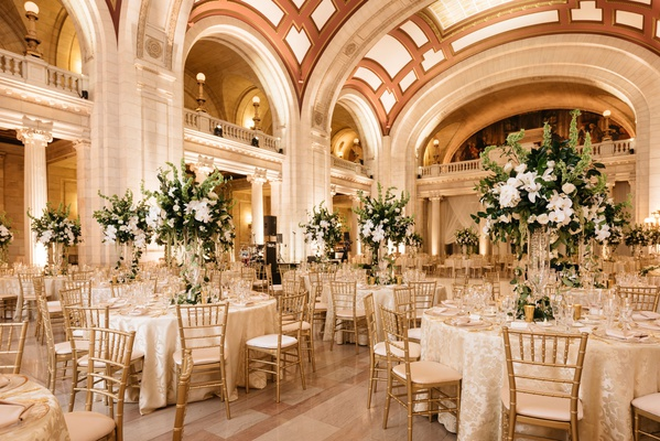 wedding reception marble hall arches columns high ceilings gold chairs tall centerpiece greenery