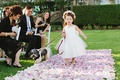 flower girl walks down purple petal aisle with dog on leash