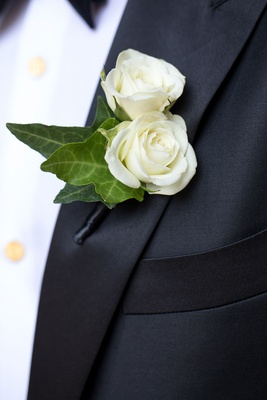 Wedding boutonniere white flowers green leaves black tuxedo lapel