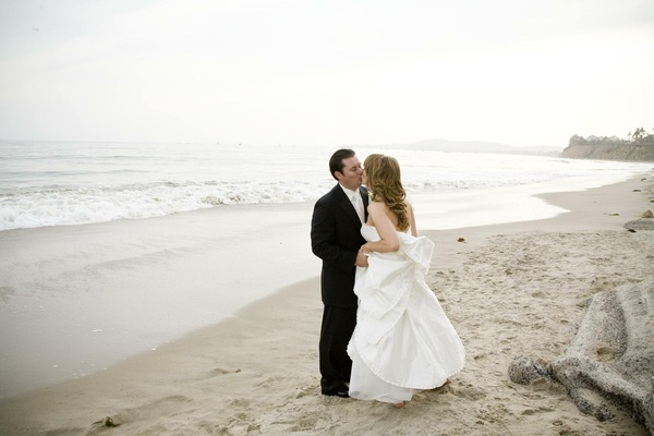 Bride and groom kiss on beach in Santa Barbara