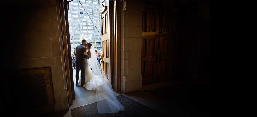 bride and groom newlyweds kiss in the doorway of chicago presbyterian church