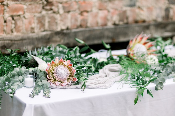 wedding reception with italian rusus, eucalyptus, and king protea blooms