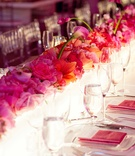 rectangular table decorated with lighted box with ombre pink flowers on top