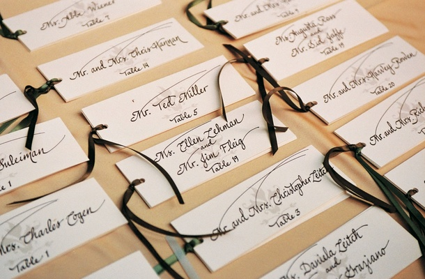 Handwritten place cards tied with ribbon