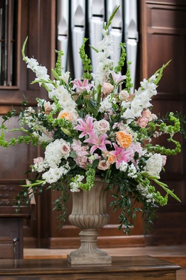 a bright floral arrangement with white pink and orange flowers in church