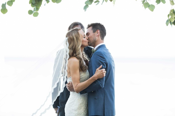 bride in pronovias and groom in ken baker kiss after being pronounced husband and wife