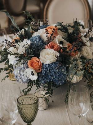 wedding reception low centerpiece blue hydrangea white anemone peach rose greenery thistle lavender