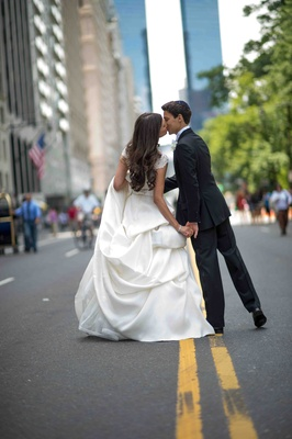 Bride in a Monique Lhuillier gown with a pick-up skirt kisses groom in a black tuxedo on the street