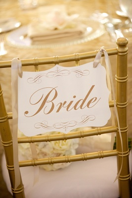 Gold bride chair with die-cut wedding stationery at reception