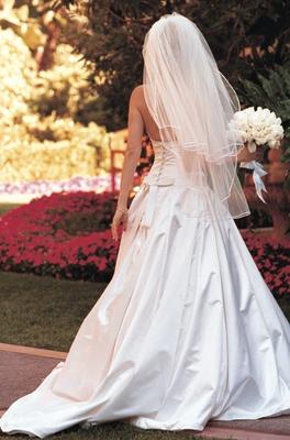 Bride in garden holding bouquet in gown